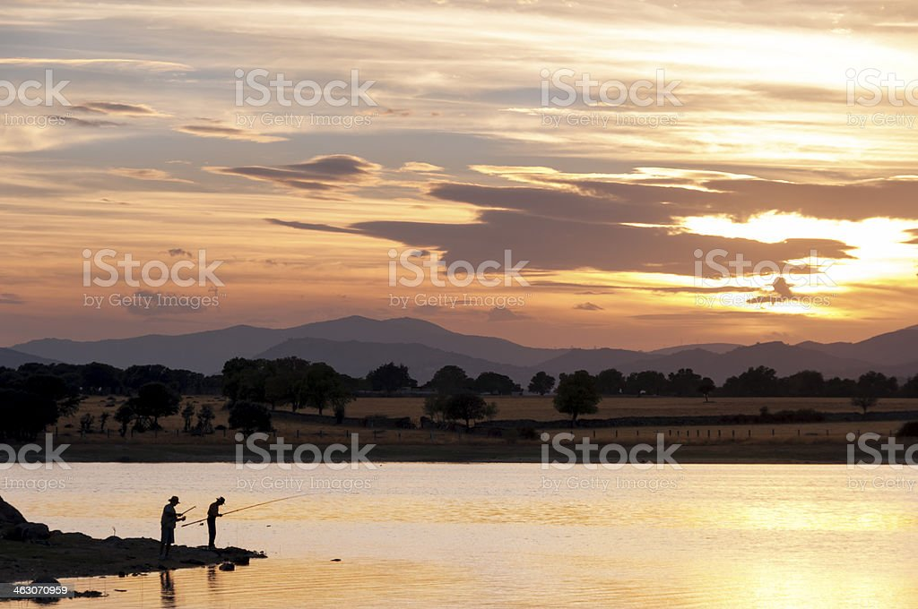 Two men fishing in the lake at sunset - 2 royalty-free stock photo