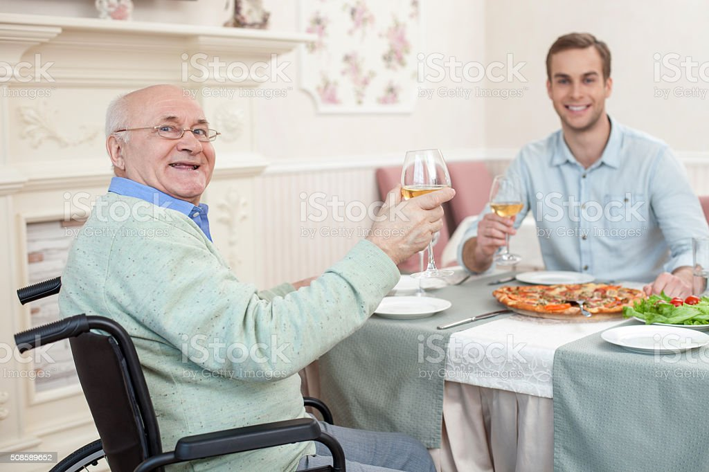 Two men have a family diner in cafe stock photo