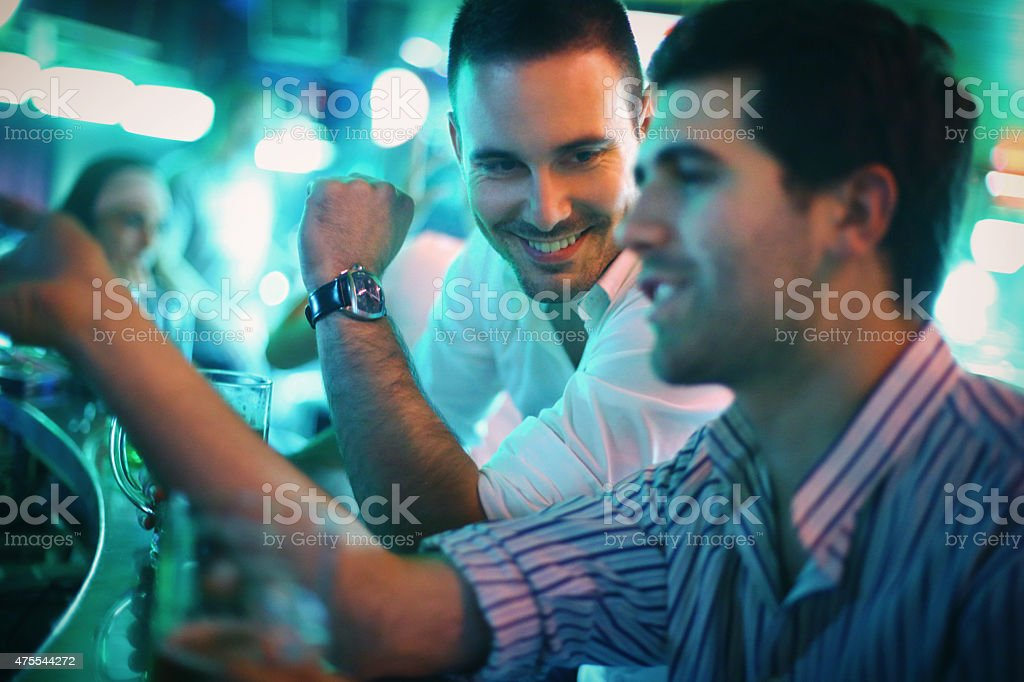 Two men having beer in a bar. stock photo