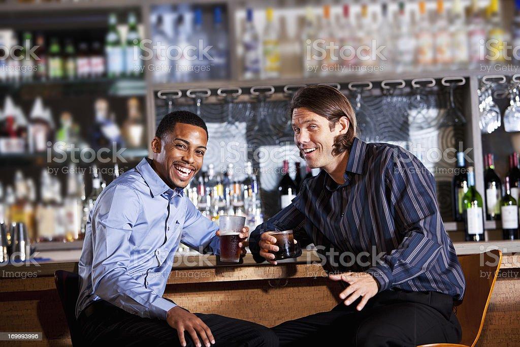 Two men having drink at bar stock photo