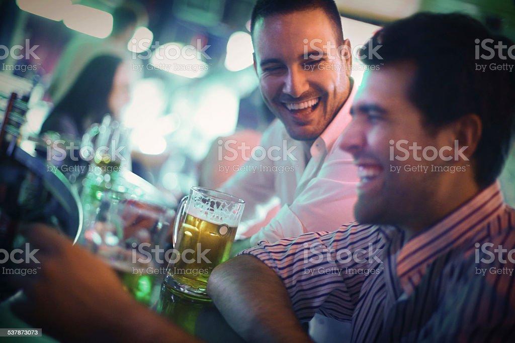Two men having fun in a bar. stock photo