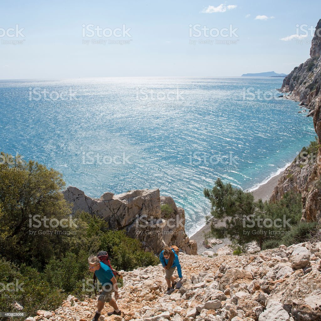 Two men hike up steep talus slope above sea stock photo