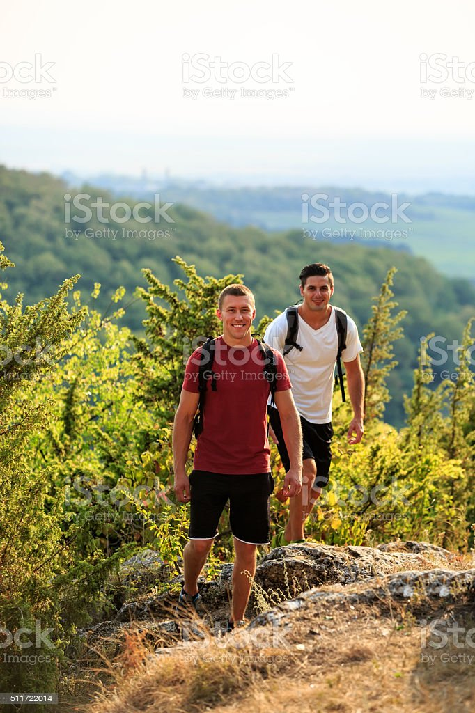 Two men hiking on the top of mountain stock photo