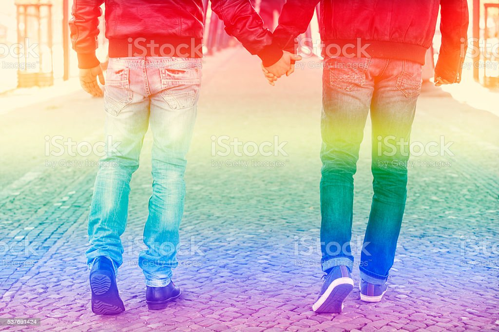 two men holding hands with rainbow colors for gay pride stock photo