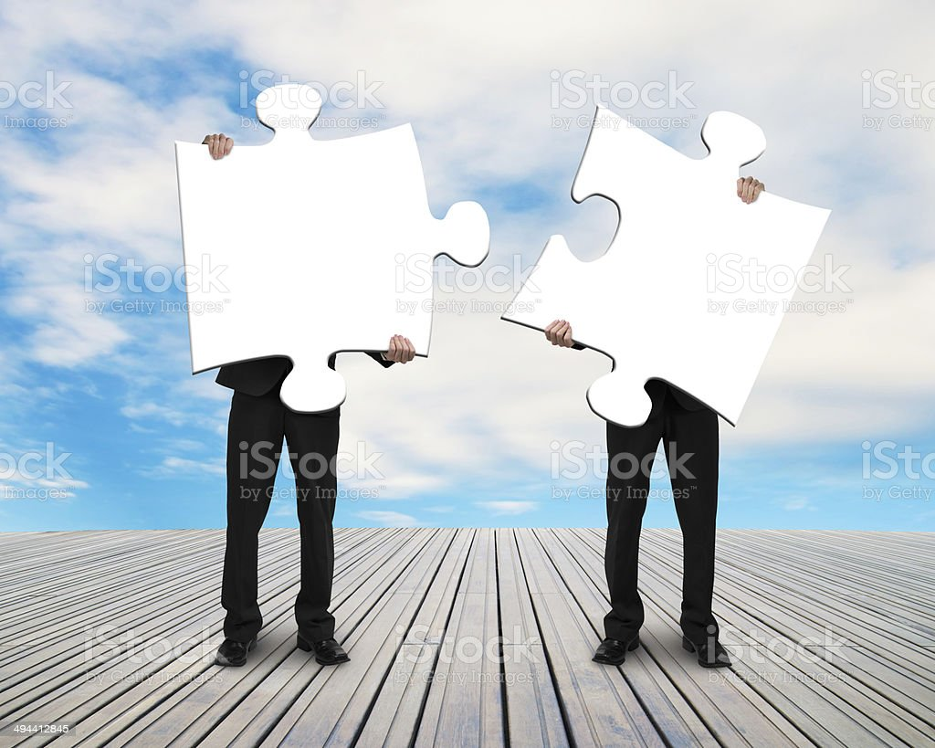 two men holding puzzles on wooden floor stock photo