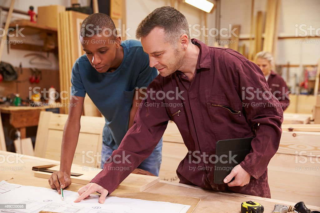 Two men in a workshop look at wood together stock photo