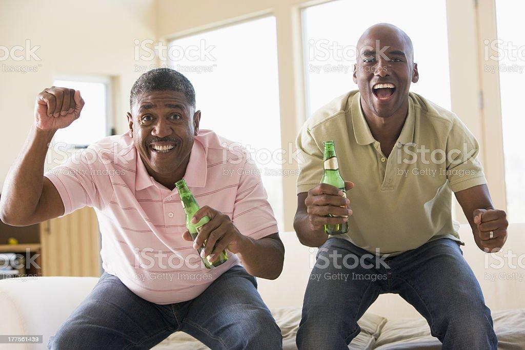 Two men in living room with beer bottles cheering stock photo
