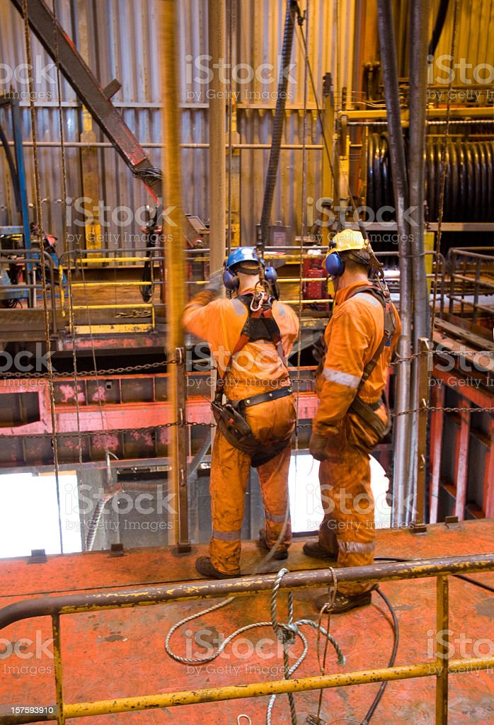 Two men in orange working on an oil rig royalty-free stock photo