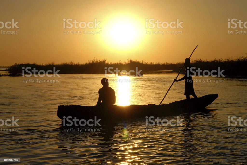 Two men in pirogue in africa stock photo