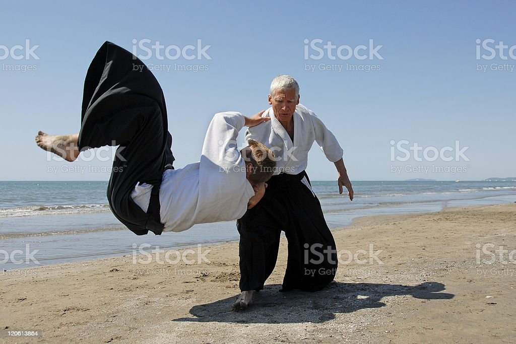 Two men in traditional aikido attire practicing on a beach stock photo