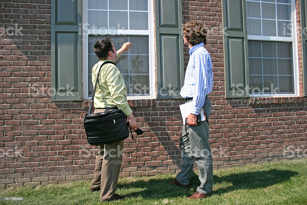 Two men inspecting a house window stock photo