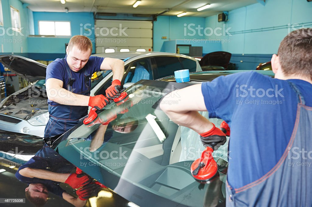 Two men installing a windshield stock photo