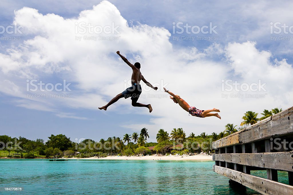 two men jumping off a dock at the Caribbean resort stock photo