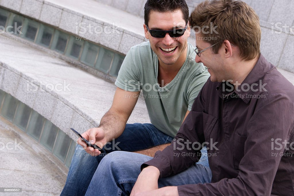 Two men laughing over text message stock photo