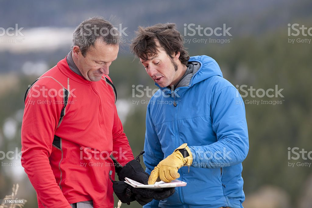 Two Men Looking at Map in the Wilderness stock photo