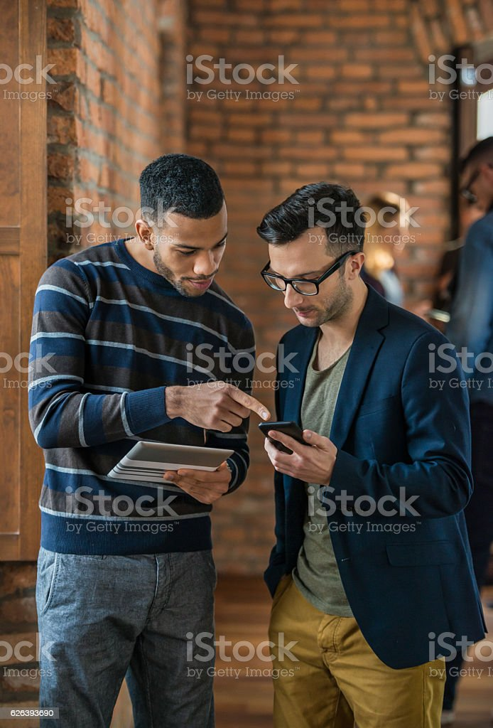 Two Men Looking In Mobile stock photo
