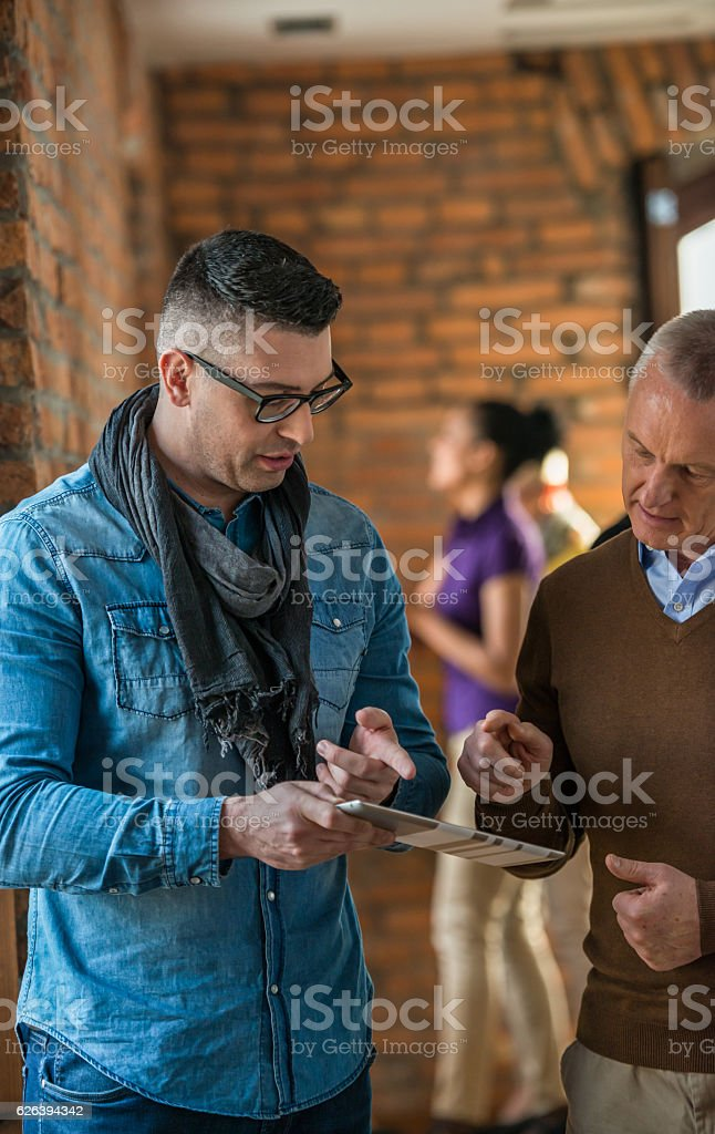 Two Men Looking In Tablet Computer stock photo