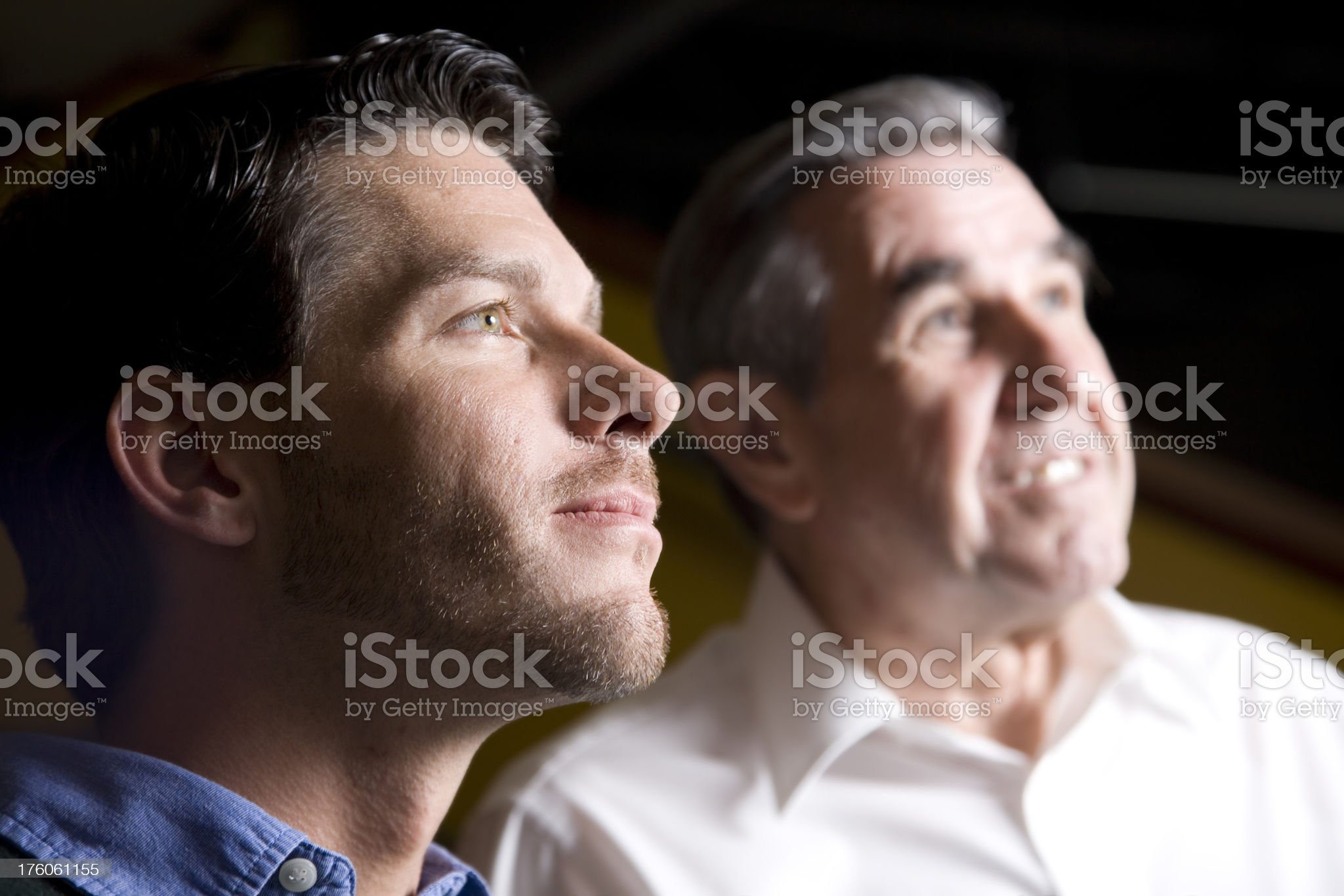 Two Men Looking Up with Light Shining on Them royalty-free stock photo