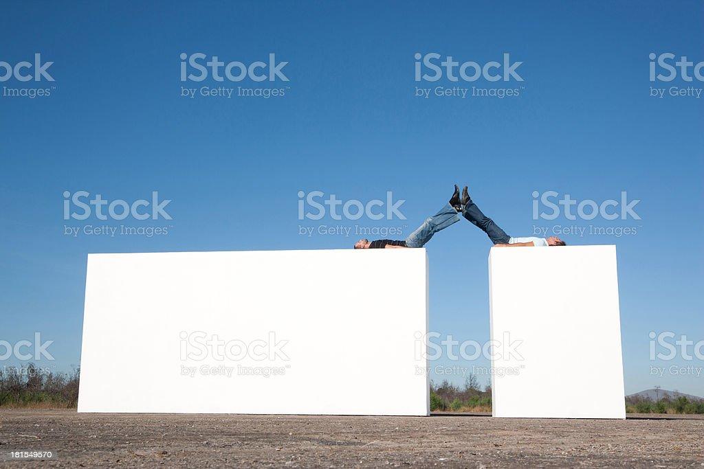 Two men lying atop blocks outdoors royalty-free stock photo