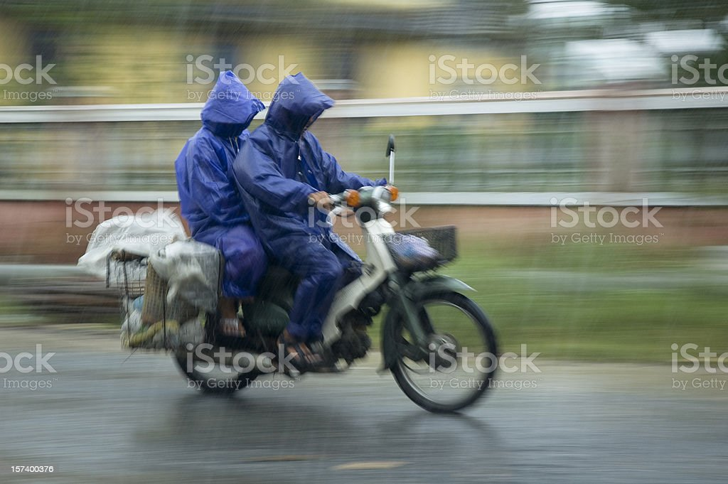 Two Men Motorcycling Through The Rain In Hoi An, Vietnam stock photo