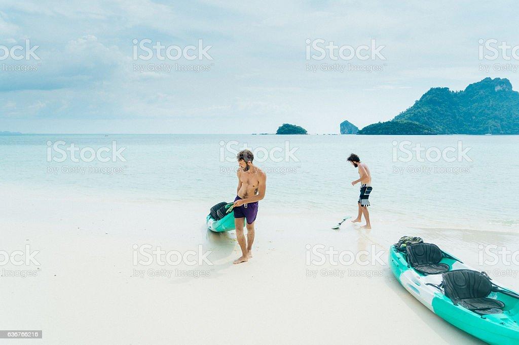Two men near kayaks stock photo