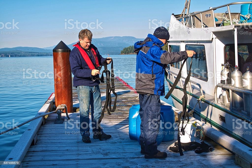 Two Men on a Dock Preparing Harnesses stock photo