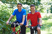 Two Men On Cycle Ride In Countryside Together