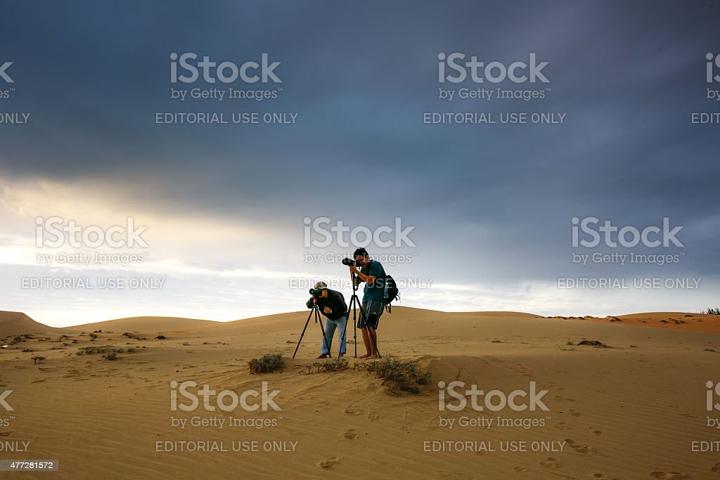 two men on sand dunes at sunrise stock photo