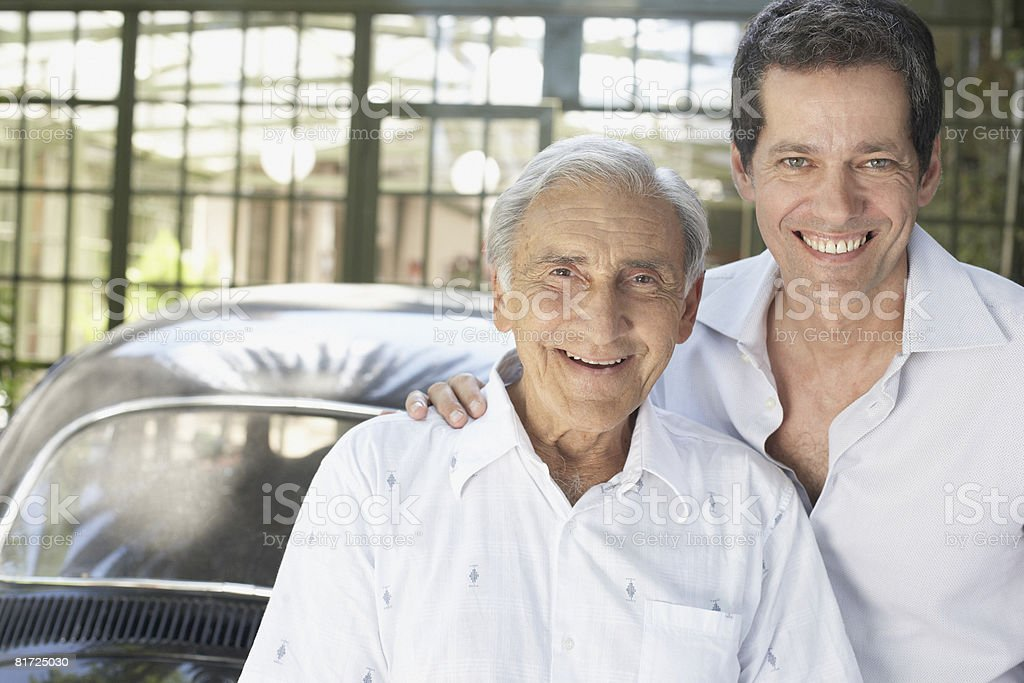 Two men outdoors leaning on car smiling royalty-free stock photo