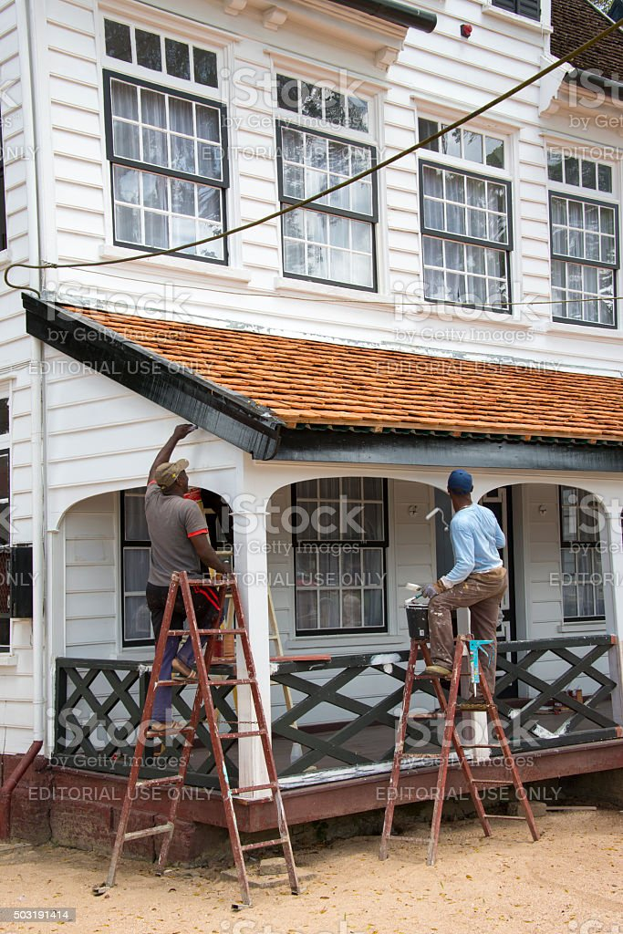 Two men painting the veranda of a historic wooden building stock photo