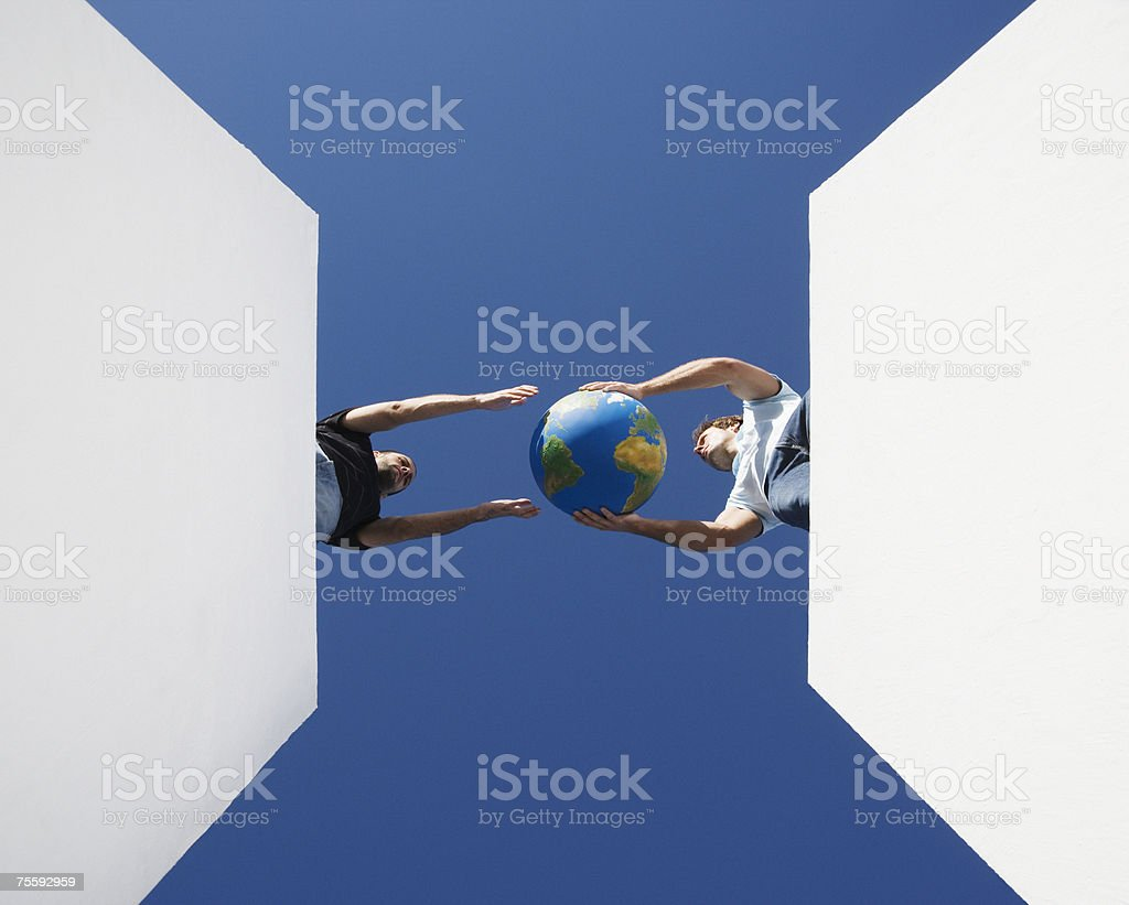 Two men passing globe outdoors from below royalty-free stock photo