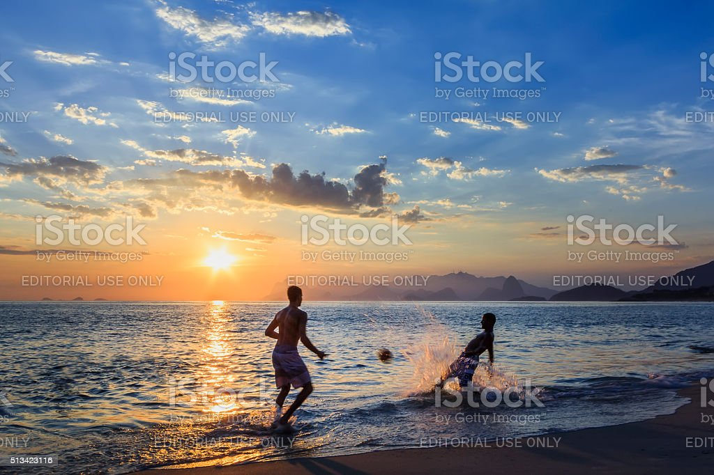 Two Men Playing Beach Football at Sunset stock photo