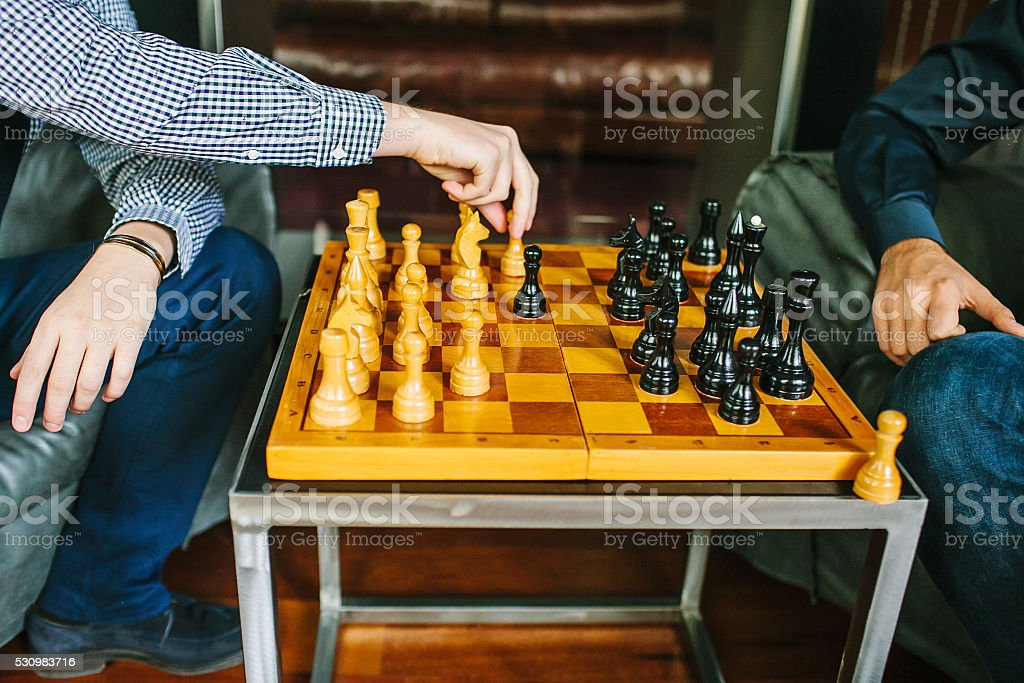 Two men playing chess inside the room. Shallow focus. stock photo