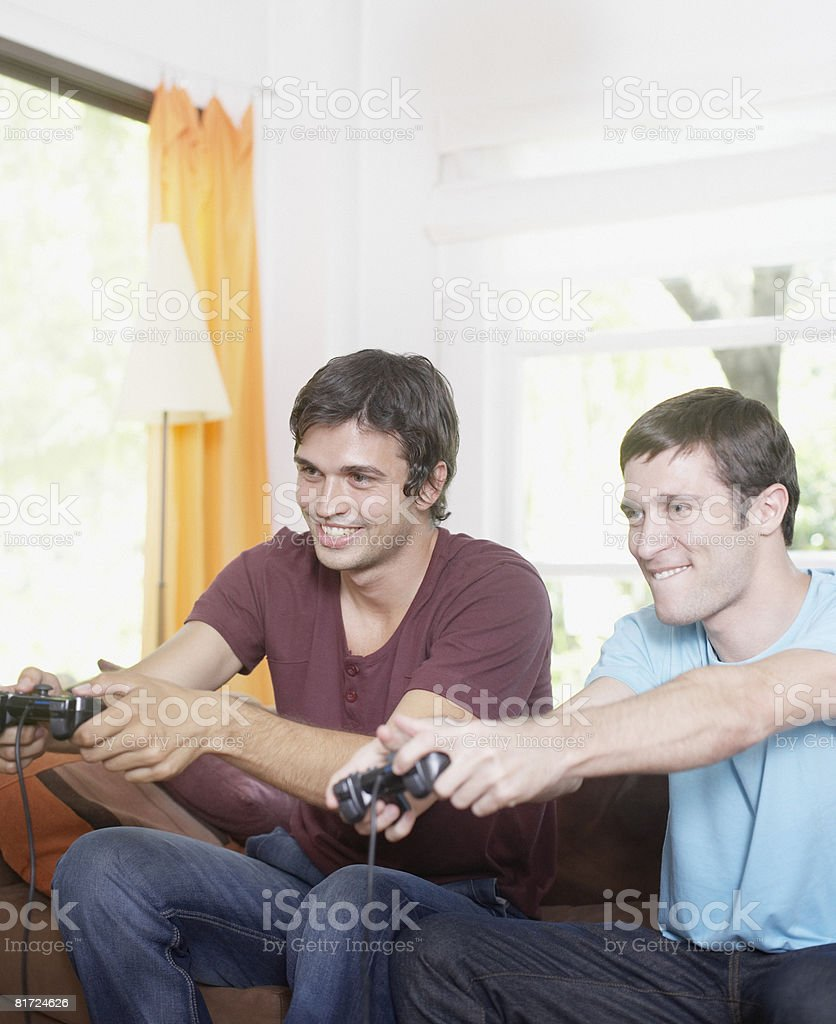 Two men playing video games in living room smiling royalty-free stock photo