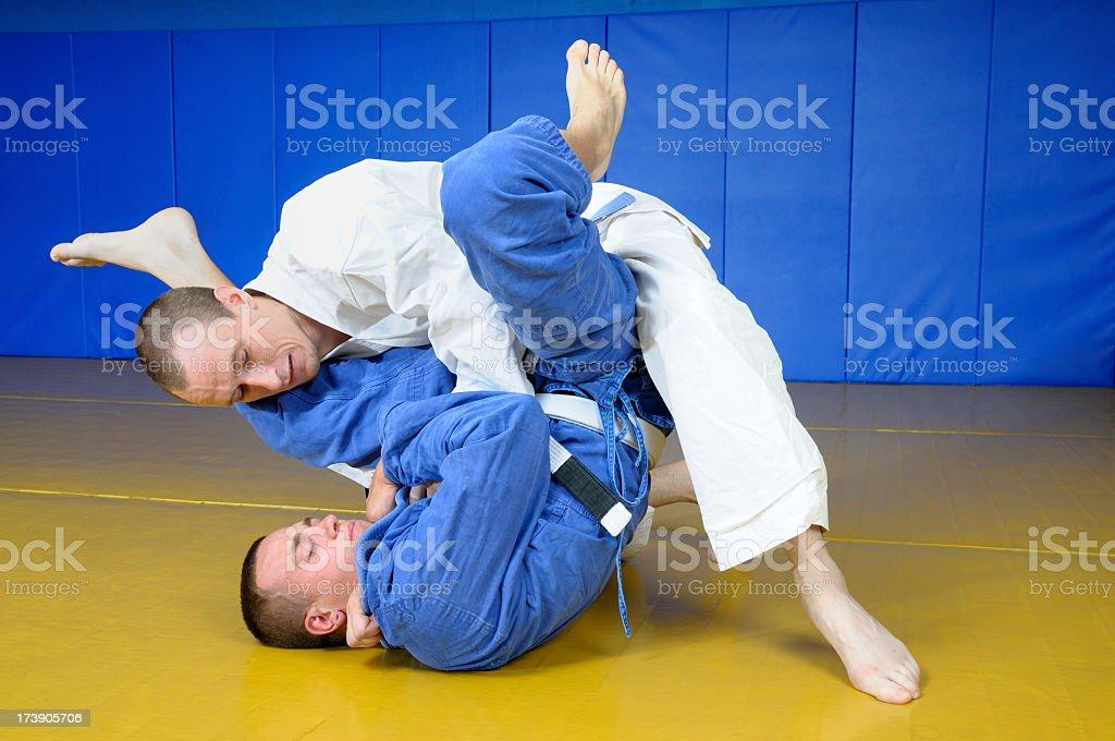 Two men practicing Jujitsu martial arts on yellow mats stock photo