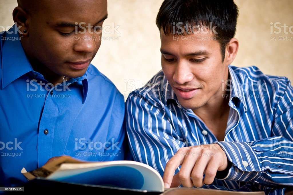 Two men reading a book with one pointing at page royalty-free stock photo