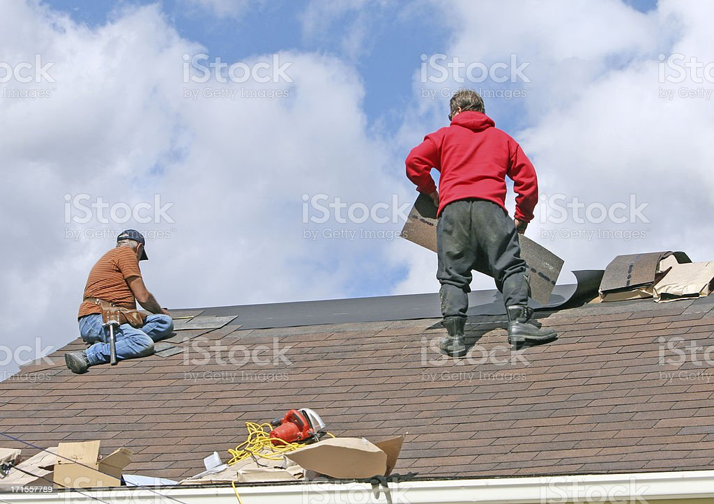 Two men replacing shingles on a house roof royalty-free stock photo