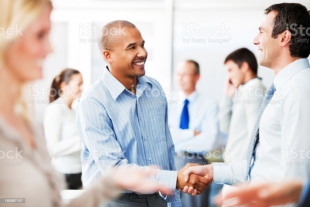 Two men shaking hands in business surroundings stock photo