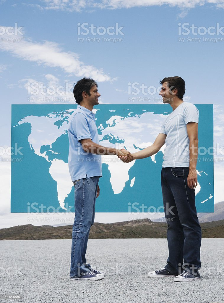 Two men shaking hands in front of world map outdoors stock photo