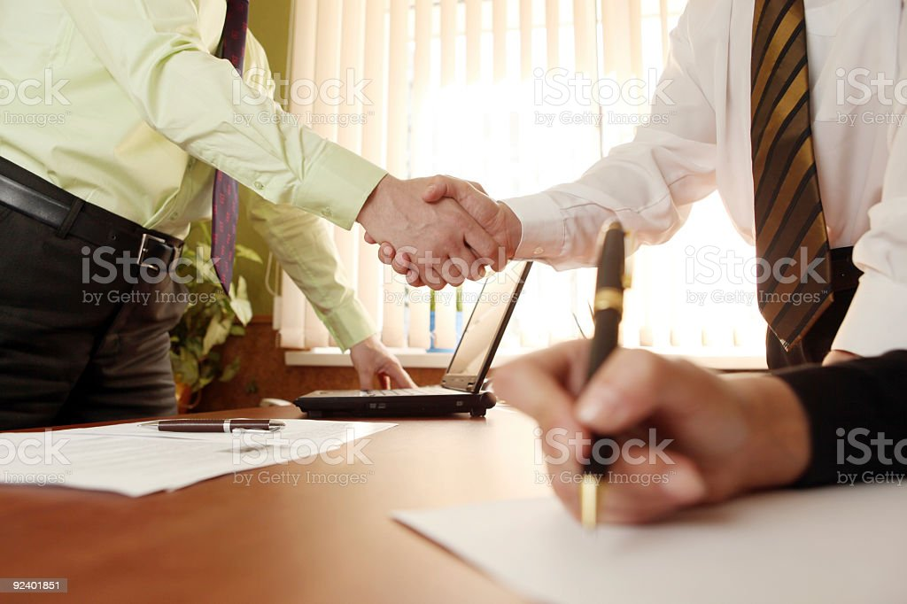 Two men shaking hands over a contract signing royalty-free stock photo