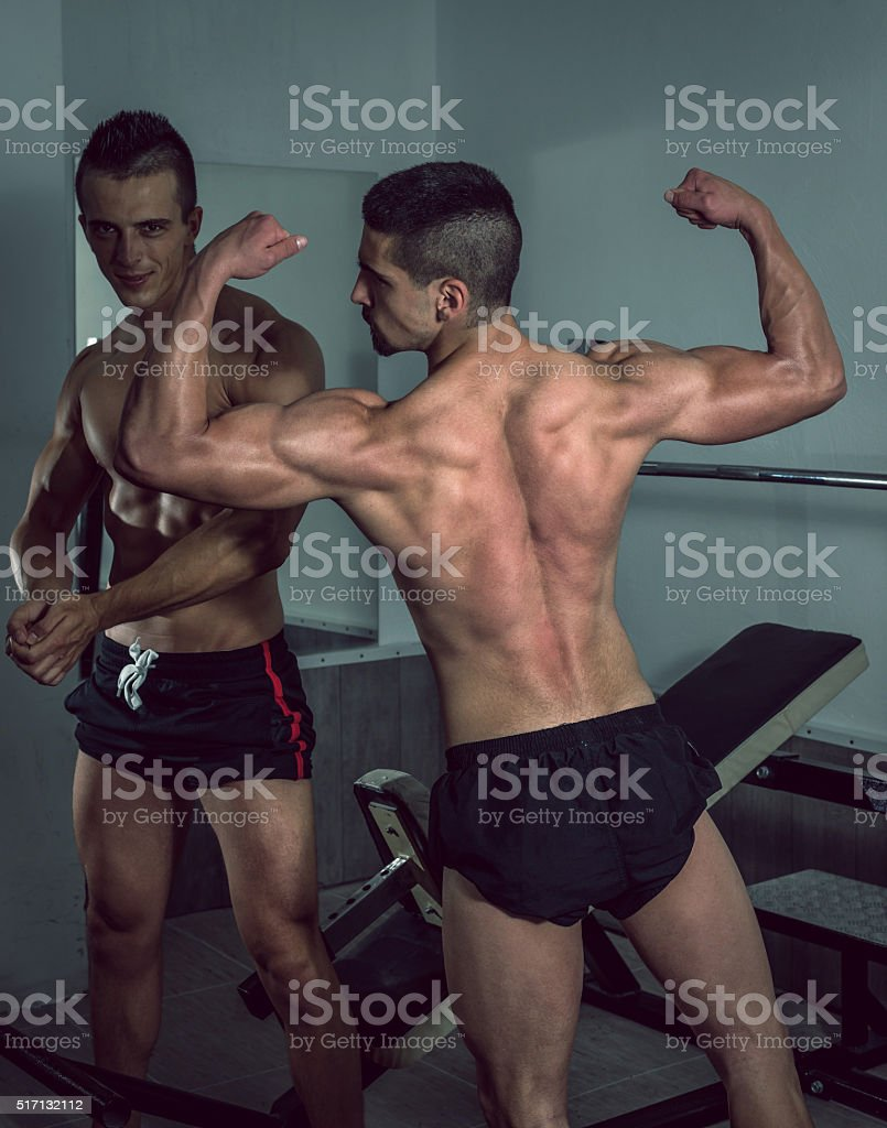 Two men showing body in gym stock photo