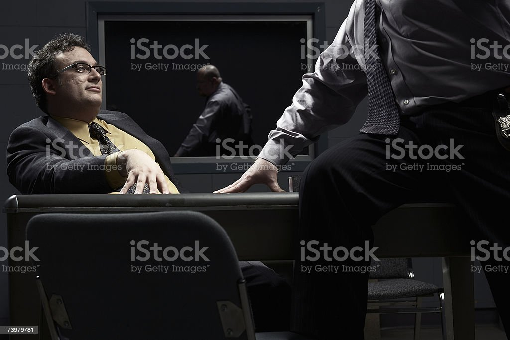 Two men sitting at desk in interrogation room stock photo