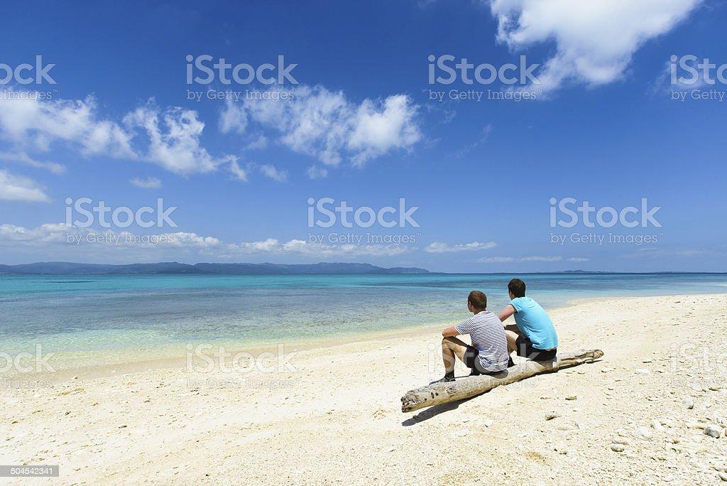 Zwei Männer sitzen auf einer idyllischen tropischen Strand Lizenzfreies stock-foto