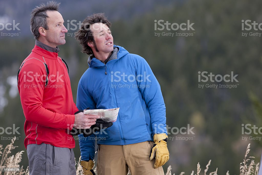 Two Men Standing in the Wilderness With a Map stock photo
