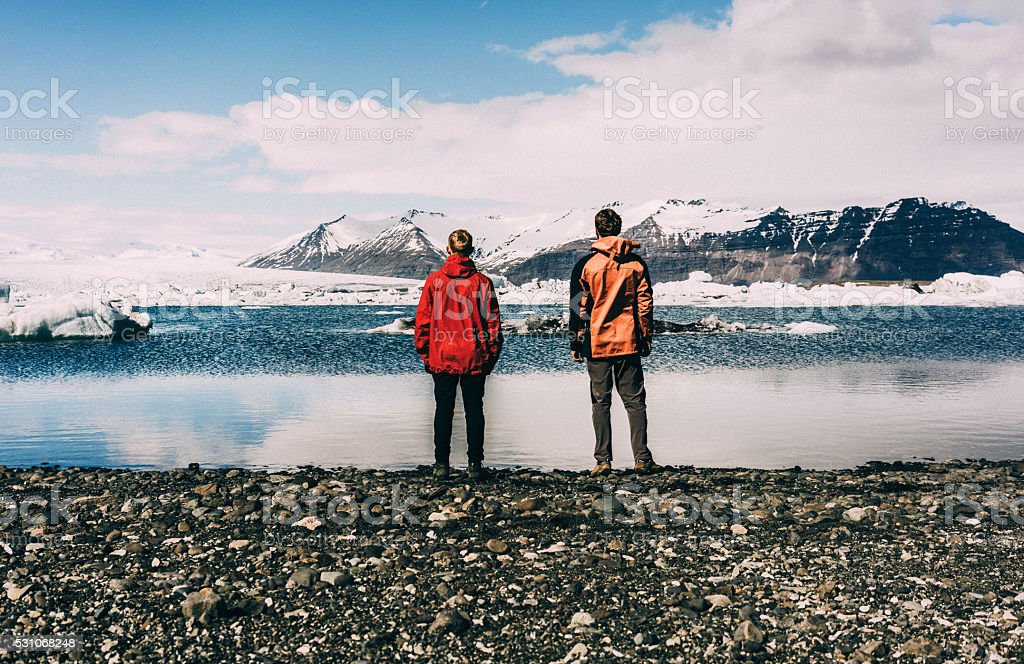 Two men standing near the lake with glaciers stock photo