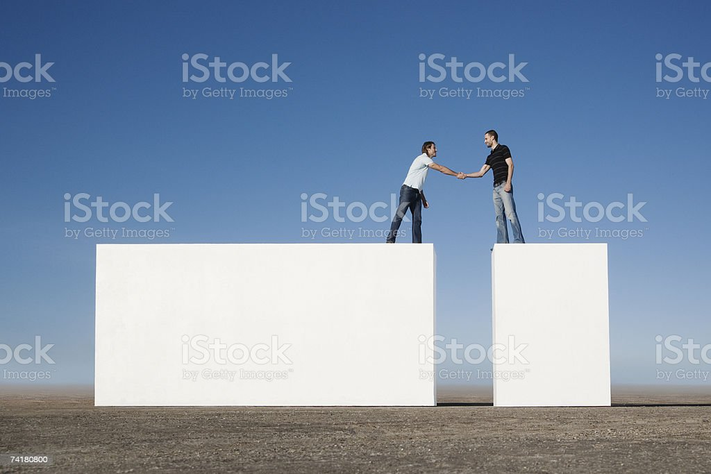Two men standing on blocks shaking hands outdoors royalty-free stock photo
