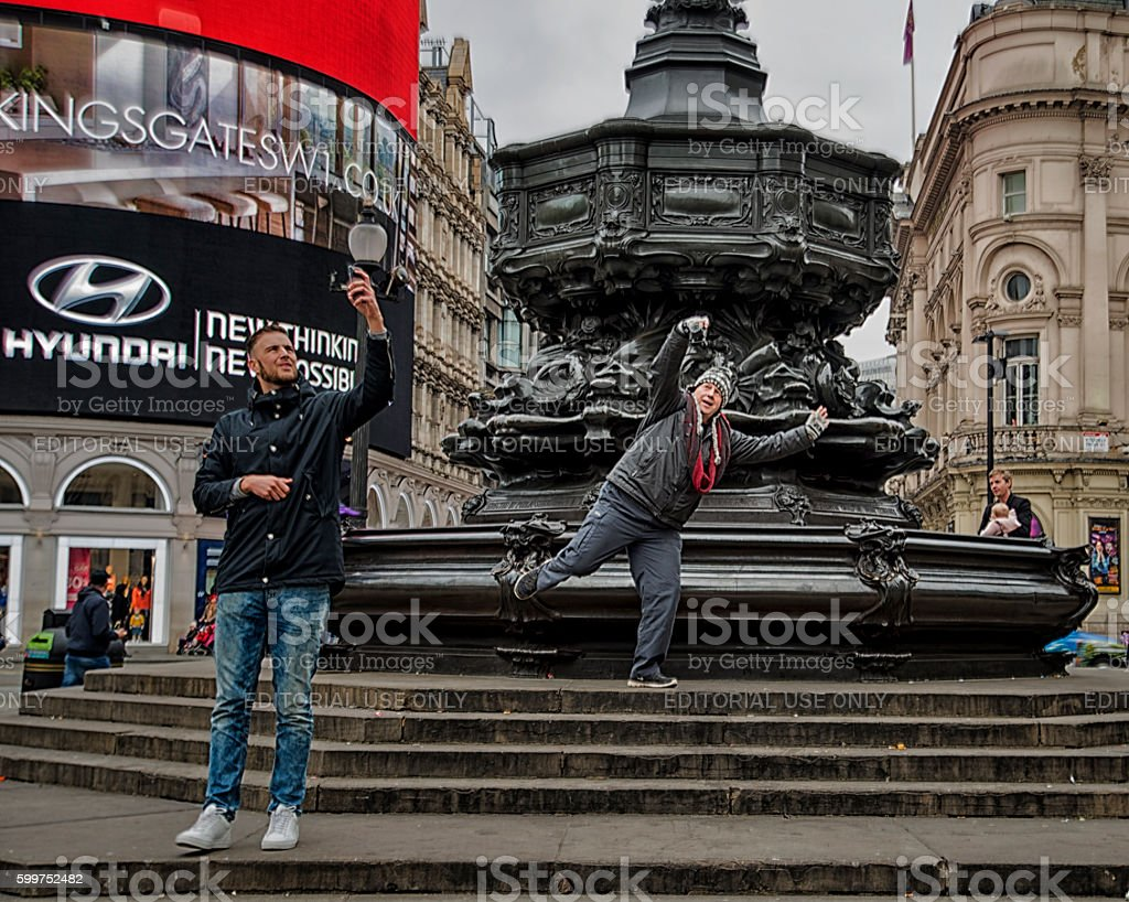 Two men taking sefies on the steps of  Eros statue stock photo