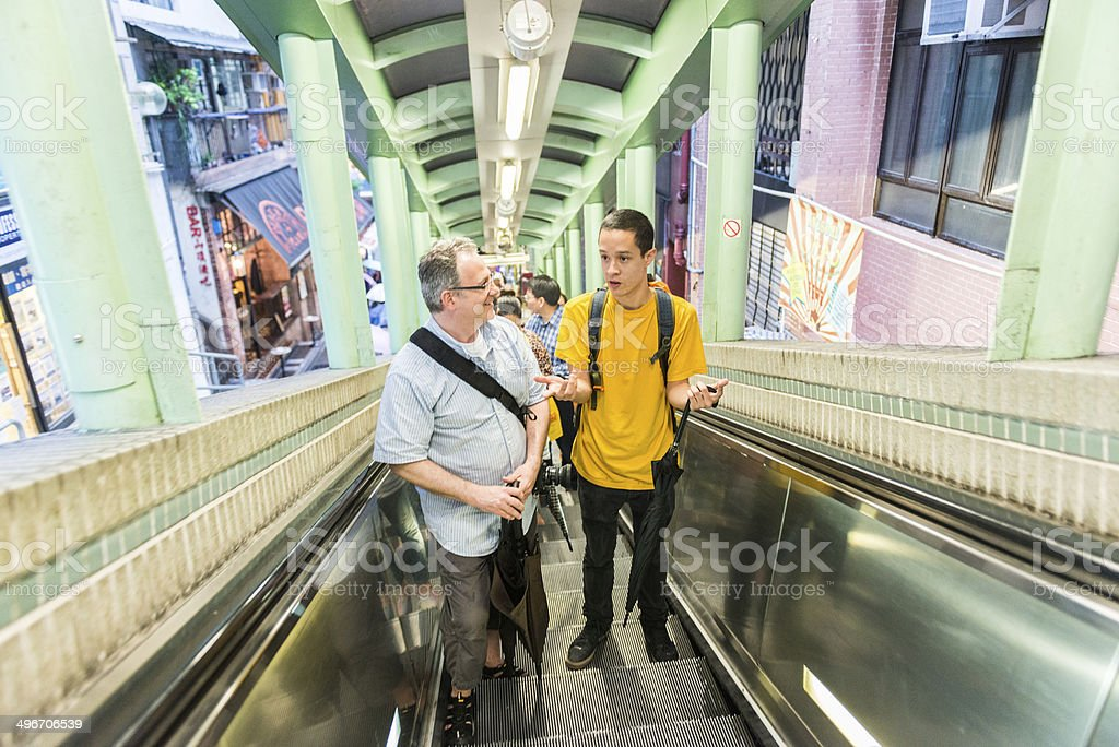 Two Men Talking While Riding the Mid-Levels Escalator stock photo
