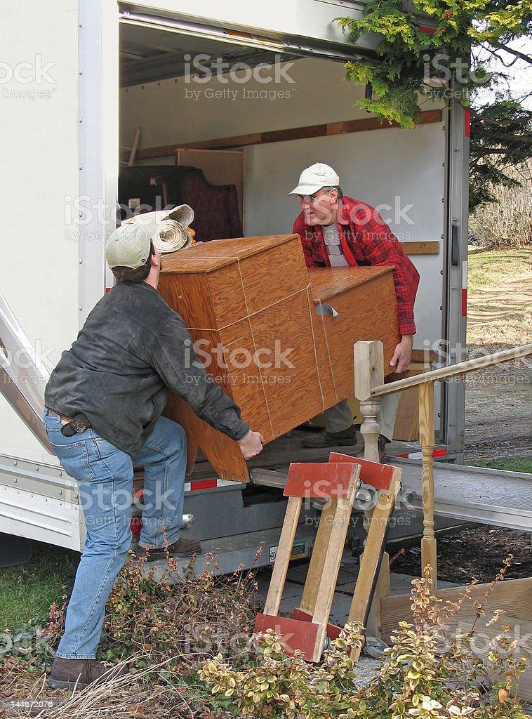 Two men unload a moving van stock photo
