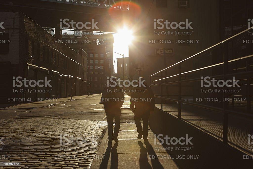 Two men walk into Brooklyn DUMBO Backstreet Sunset lens flare stock photo